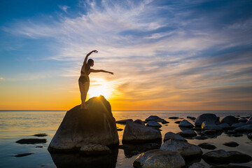 Graceful woman dancing on boulder during sundown