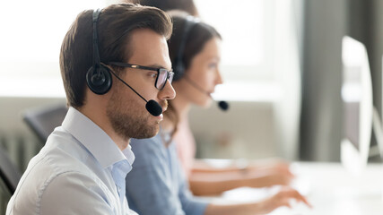 Obraz Confident call center operator agent in headset with microphone consulting client online close up, busy employee working in customer support service office, coworking space, horizontal photo - fototapety do salonu