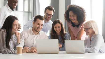 Happy smiling diverse employees using laptop, watching webinar together, engaged in online...
