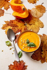 Bowl of pumpkin or carrot vegetarian cream soup decorated by fresh basil, olive oil and pumpkin seeds on white texture background with yellow autumn maple leaves above.