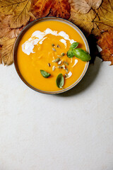 Bowl of pumpkin or carrot vegetarian cream soup decorated by fresh basil, cream and pumpkin seeds on white texture background with yellow autumn maple leaves above. Flat lay, copy space