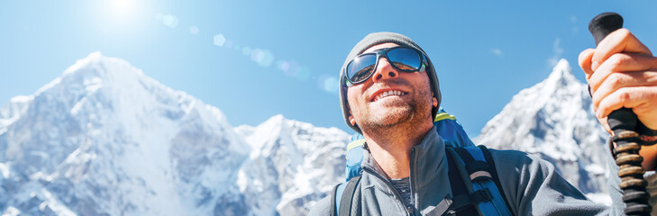 Portrait of smiling Hiker man on Taboche 6495m and Cholatse 6440m peaks background with trekking poles, UV protecting sunglasses. He enjoying mountain views during Everest Base Camp trekking route. Wall mural