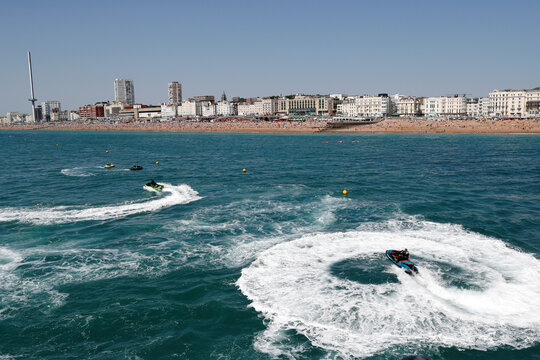 People ride on jet skis as they enjoy the sunny weather at a beach in Brighton