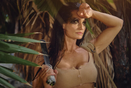 Middle aged sporty tired female wear sexy top holding machete knife posing on wild nature tropical palm trees jungle forest. Spirit of adventure. Survivor woman concept