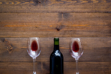 Fototapete - Wine bottle and glasses on wooden background from above copy space