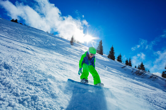 Active boy move fast on snowboard throwing snow around - motion image over blue sky and ski slope panorama