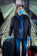 Full-height portrait of a middle-aged in a blue protective mask just gone down the escalator to a subway platform