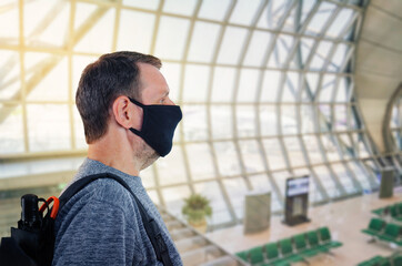 Close-up side portrait of a man wearing a black protective mask at an airport