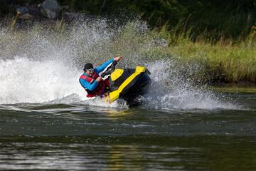 Man on jet ski turns with much splashes.