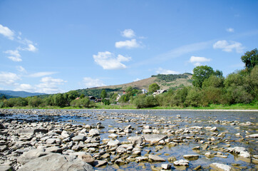 Landscape photo of a rocky mountain river, in the summer under the sun, view from the water level