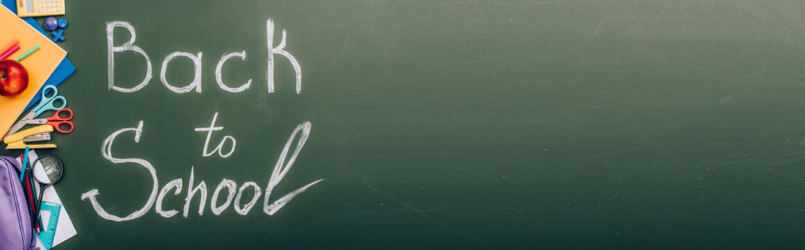 top view of back to school lettering near school stationery on green chalkboard, panoramic shot
