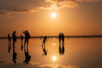 Beautiful sunset on the lake, the sun reflecting in the water, silhouettes of people reflected in the water