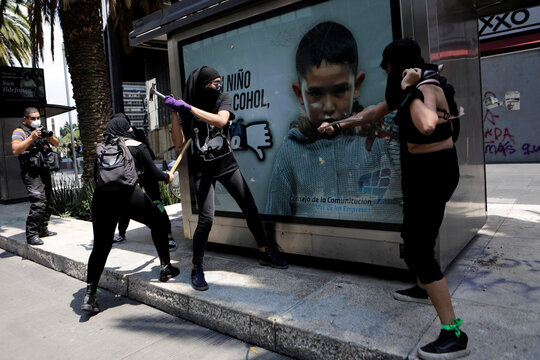 Women vandalize a billboard during a march toward the Mexico's Supreme Court after judges voted down an injunction that could have decriminalized abortion in the conservative state of Veracruz, in Mexico City