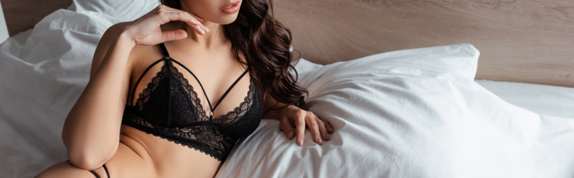Panoramic crop of sexy woman in lace bra lying on bed in bedroom