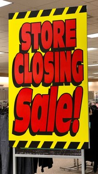Yellow and red store closing sign is displayed at a retail store that is going out of business