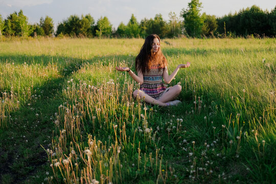 Young woman practicing yoga sitting in easy pose outdoors in green field. Unity with nature concept.