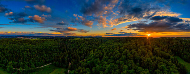 Awesome sunset over a forest at summertime, panoramic arial view with dramatic clouds.