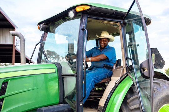 Portrait of mature man and tractor on farm