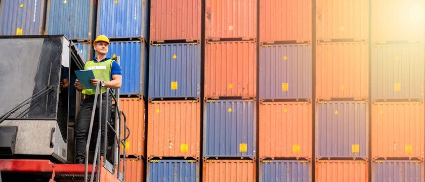Portrait of confident inspector standing in front of containers in port, Dock worker with clipboard checking cargo freight shipping, Concept of transportation, logistics business. 21:9 wide photo