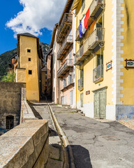A steep and narrow alley with colorful traditional houses in Briancon old town, Hautes-Alpes, France
