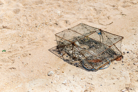 an iron old crab trap lies on a sandy beach, the traditional way of catching