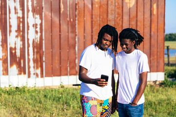 Brothers chatting on farm looking at smartphone
