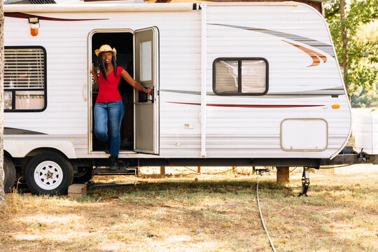 Woman walking out of camper trailer in rural America
