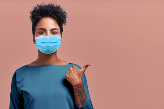 Portrait of Kind Hearted African American Female Paramedic Wearing a Respiratory Mask from Coronavirus Disease During COVID-19 Pandemic, Shows Something Amazing at Blank Space, on Beige Background.