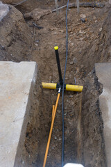 Two plastic pipes in a sand ditch.