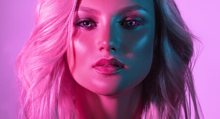Beautiful girl in a neon light, blue and violet colors. Palette of tints in the bright make up on...