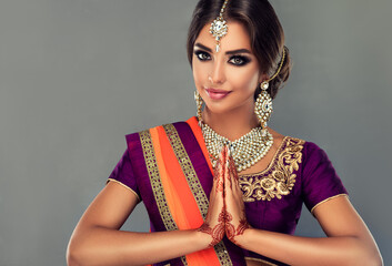 Photo sur Plexiglas Kiev Portrait of a beautiful indian girl in a greetting pose to Namaste .India woman in traditional sari dress and jewelry.