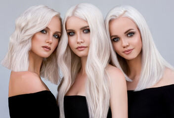 Three beautiful girls with hair coloring in ultra blond. Stylish hairstyle curls done in a beauty...