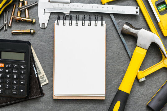 Construction cost or repair calculation mockup. Blank page notepad and work tools on the workbench.