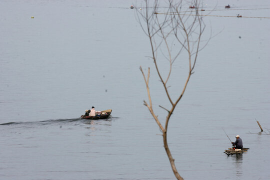 A fisherman (right) and a food trader go around by boat in the Jatiluhur Reservoir, Purwakarta, West Java, Indonesia.