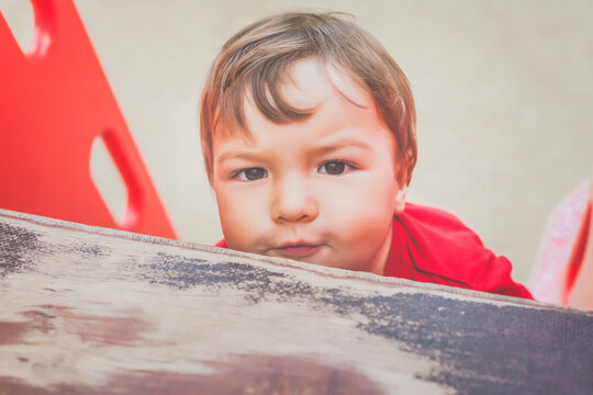 portrait of cute little boy in red t-shirt excitedly playing on playground. concept of happy healthy child