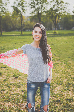 Beautiful hipster girl in red plaid shirt, grey t-shirt and ripped blue jeans in a casual style posing in green nature