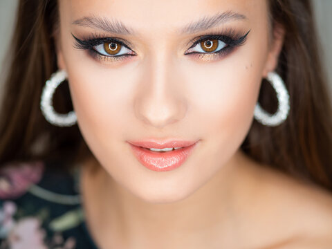 Portrait of a young beautiful brunette woman with bright eye makeup.