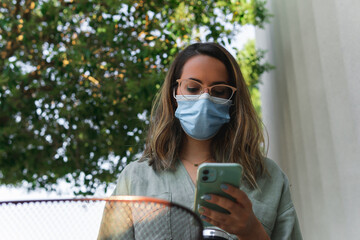 Young girl with glasses and face protection mask looking at her smartphone