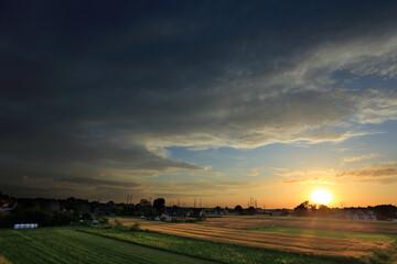 Zachód słońca nad wioską i polami.