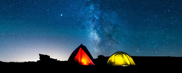 Tents glowing under the milky way at night. Camping in the mountains under the starry magical sky. Camping and wild life concept. Real outdoor adventure.