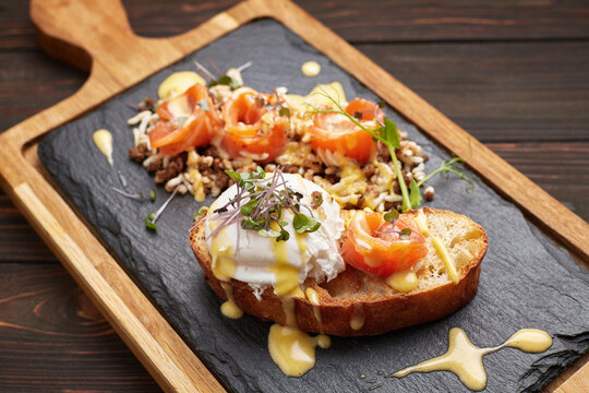 Bruschetta with salmon, poached egg and dye rice. on a wooden board