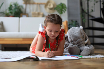 Smilling happy girl lying on warm floor with a toy elephant near to her enjoying creative activity, drawing pencils coloring pictures in albums.