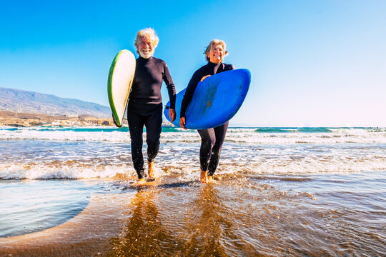 two old and mature people having fun and enjoying their vacations outdoors at the beach wearing wetsuits and holding a surfboard to go surfing in the water with waves - active senior smiling and enjoy