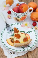 Aprikosentarte auf einem Teller und frische Aprikosen