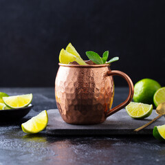 Moscow Mules cocktail with ginger beer, vodka, lime and mint. Grey background. Close up.