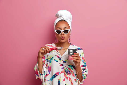 Indoor shot of lovely dark skinned young lady keeps lips folded, has good appetite as eats delicious frozen ice cream, wears trendy sunglasses, domestic outfit isolated on pink background. Summer time