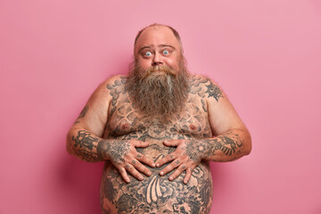 Bearded thick guy keeps hands on big tattoed belly, has bugged eyes, has thick beard, poses against pink background. Naked overweight adult man with large tummy, asks advice how to loose weight