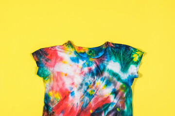 T-shirt with short sleeves in tie dye style on a yellow background. Flat lay.