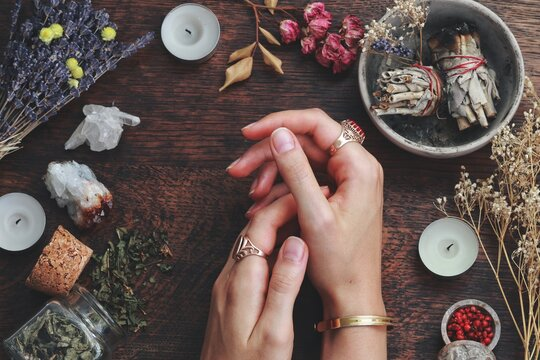 Witches hands on a table ready for spell work. Wiccan witch altar filled with sage smudge sticks, herbs, white candles. Female witch wearing vintage jewellery, placing her hands on dark wooden table