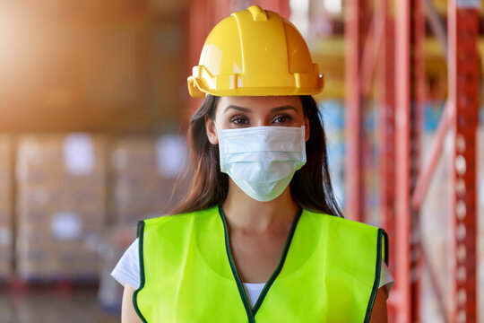 Young Attractive Hispanic Latin ethnic women wearing protective face mask during working in warehouse, new normal after Covid-19 pandemic crisis. Logistic industry concept.